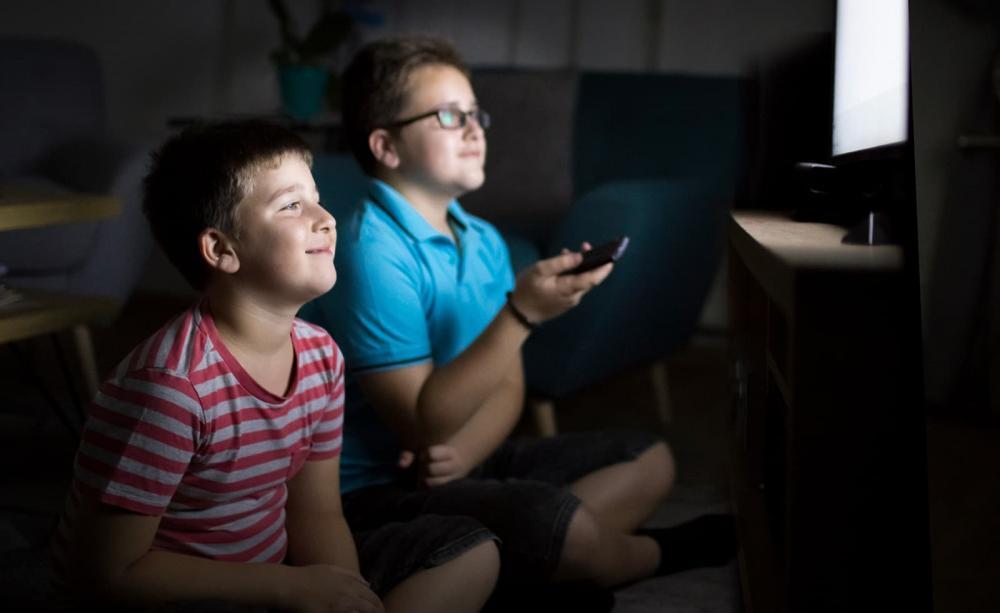 Tweens boys sit and watch TV
